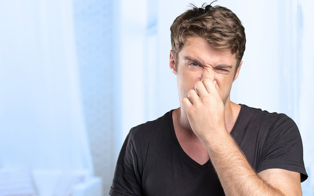 Guy plugging nose because of bad smell